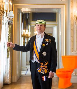 Staatsiefoto, met Rijkskaasschaaf, de Driekleur, kroon en de eerder verworpen troon toiletpot.