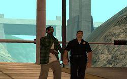 Policial andando pela rua, note sua preocupação com o cidadão armado ao lado.