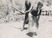 Woman spanks her friend with a paddle.jpg